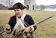 Newburgh, New York  - A Revolutionary War reenactor in uniform talks about his musket at Washington's Headquarters State Historic Site  as part of George Washington's birthday celebration on Feb. 18, 2012.  The man is a member of John Lamb's Artillery Company. The Tower of Victory monument and the Hudson River are visible in the background.