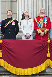 © London News Pictures.. 14/06/2014. L to R Prince Harry, Catherine Duchess of Cambridge and Prince William on the balcony of Buckingham Palace during the annual Trooping the Colour Ceremony in central London. The event marks the queens official birthday. . Photo credit:Ben Cawthra/LNP