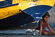 A young girl sits on the beach next to a colorful wooden fishing boat near Sao Filipe, Fogo Island, Cape Verde, on Thursday December 30, 2010.