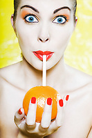 beautiful caucasian woman portrait  amazed drinking with a straw in an orange studio on yellow background