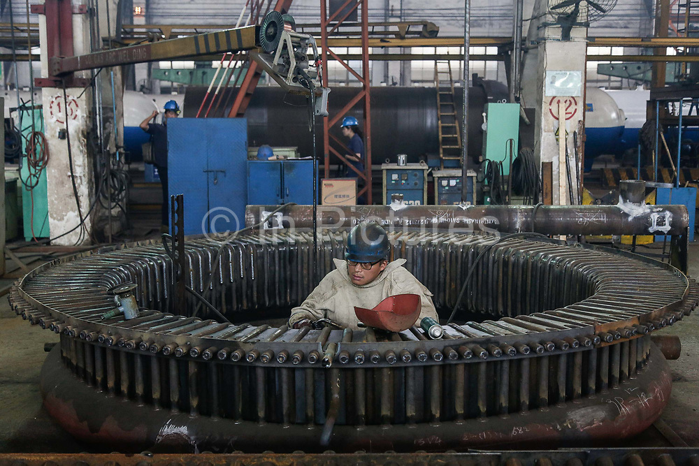 A worker welds a burner section of a boiler at a factory in Wuxi, Jiangsu Province, China on 26 September 2012.