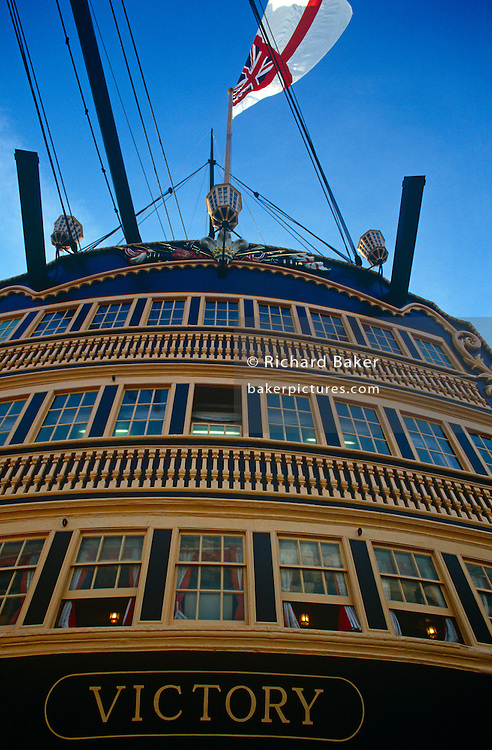 The stern of Admiral Lord Nelson's flagship HMS Victory at Portsmouth. We look up at the rear of Britain's most famous warship from the Napoleonic war era and see the windows of Nelson's cabins and rooms - the location where the battle of Trafalgar was planned and where Nelson died on that day in 1805. Victory took Nelson's body to England where, after lying in state at Greenwich, he was buried in St. Paul's Cathedral on 6 January 1806..HMS Victory is a 104-gun first-rate ship of the line of the Royal Navy, laid down in 1759 and launched in 1765. After Trafalgar, she served as a harbour ship, moved in 1922  to a dry dock at Portsmouth, England, and preserved as a museum ship. She is the flagship of the First Sea Lord and is the oldest naval ship still in commission