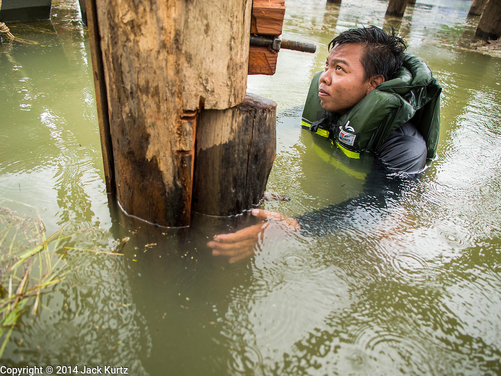 16 SEPTEMBER 2014 - SANGKHLA BURI, KANCHANABURI, THAILAND: A Thai army safety swimmer in the water during the repair of the Mon Bridge. The 2800 foot long (850 meters) Saphan Mon (Mon Bridge) spans the Song Kalia River. It is reportedly second longest wooden bridge in the world. The bridge was severely damaged during heavy rainfall in July 2013 when its 230 foot middle section  (70 meters) collapsed during flooding. Officially known as Uttamanusorn Bridge, the bridge has been used by people in Sangkhla Buri (also known as Sangkhlaburi) for 20 years. The bridge was was conceived by Luang Pho Uttama, the late abbot of of Wat Wang Wiwekaram, and was built by hand by Mon refugees from Myanmar (then Burma). The wooden bridge is one of the leading tourist attractions in Kanchanaburi province. The loss of the bridge has hurt the economy of the Mon community opposite Sangkhla Buri. The repair has taken far longer than expected. Thai Prime Minister General Prayuth Chan-ocha ordered an engineer unit of the Royal Thai Army to help the local Mon population repair the bridge. Local people said they hope the bridge is repaired by the end November, which is when the tourist season starts.    PHOTO BY JACK KURTZ