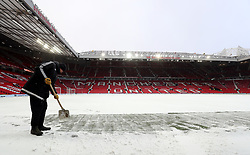 Ground Staff remove snow on the pitch before the Emirates FA Cup, quarter final match at Old Trafford, Manchester.