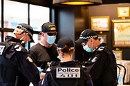 MELBOURNE, VIC - SEPTEMBER 20: Police question a man inside a cafe in the Chadstone Shopping Centre during a series of pop up Freedom protests on September 20, 2020 in Melbourne, Australia. Freedom protests are being held in Melbourne every Saturday and Sunday in response to the governments COVID-19 restrictions and continuing removal of liberties despite new cases being on the decline. Victoria recorded a further 14 new cases overnight along with 7 deaths. (Photo by Dave Hewison/Speed Media)