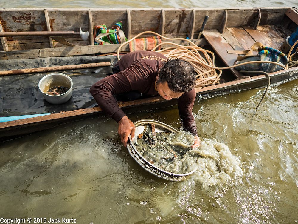 14 OCTOBER 2015 - BANGKOK, THAILAND: A diver sluices things he brought up from the bottom of the Chao Phraya River in Bangkok, looking for anything he can sell. Divers work in two man teams on small boats in the Chao Phraya River. One person stays in the boat while the diver scours the river bottom for anything that can be salvaged and resold. The divers usually work close to shore because the center of the river is a busy commercial waterway with passenger boats and commercial freight barges passing up and down the river all day long. The Chao Phraya is a dangerous river to dive in. It's deep, has large tidal fluctuations, is fast flowing and badly polluted. The divers make money only when they sell something.    PHOTO BY JACK KURTZ