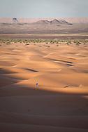 Berber walking across sand dunes, Merzouga, Sahara Desert, Morocco