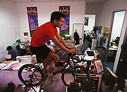 Scott Hublou (M.R.), Founder and CEO of ASIMBA.com, a Silicon Valley start-up. Training for Iron-man in his cramped office, he is able to do email at the same time. (1999).