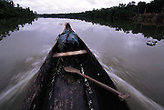 The narrow prow of a bongo, a 30 foot-long dugout canoe, pushes up the Orinoco River and deep into the rain forest home of the Yanomami in southeast Venezuela. (Man Eating Bugs page 166,167) .