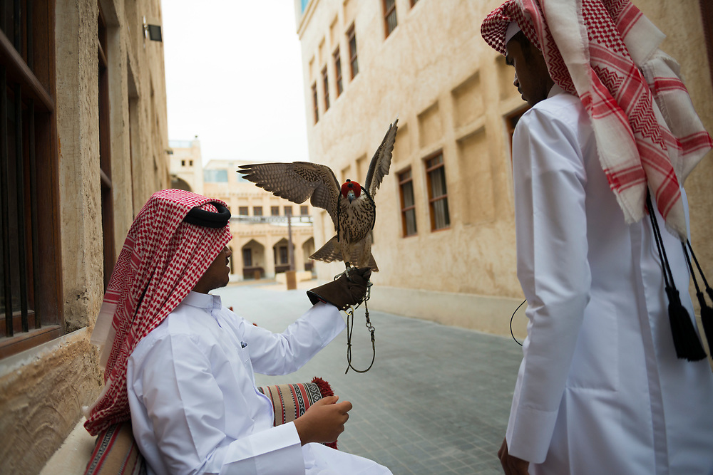 Two young Qataris, one holding a falcon, wait outside the falcon hospital in the Falcon Souk in Souk Waqif in Doha, Qatar