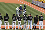 04 June 2016: After throwing out a ceremonial first pitch, Nova Southeastern Director of Athletics Michael Mominey (center) is presented with the ball by catcher Jake Anchia (right). The Nova Southeastern University Sharks played the Millersville University Marauders in Game 14 of the 2016 NCAA Division II College World Series  at Coleman Field at the USA Baseball National Training Complex in Cary, North Carolina. Nova Southeastern won the game 8-6 and clinched the NCAA Division II Baseball Championship.