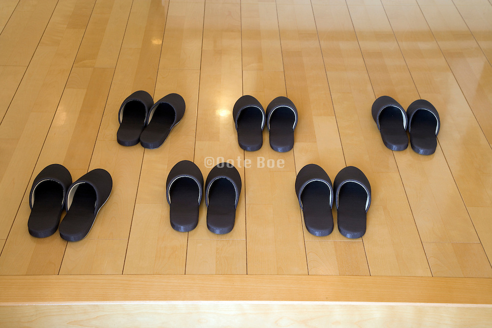 rows of slippers at the entrance to a residential house waiting for the guests