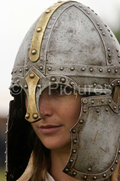 A member of a Roman re-enactment society in a period helmet at Richborough Roman Fort, Kent, UK