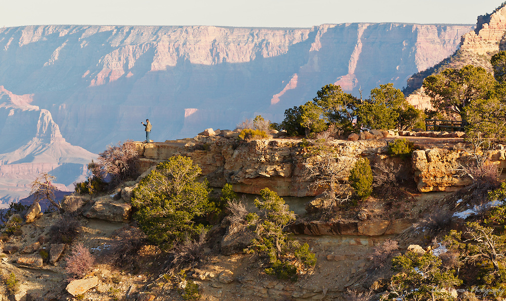 A tourist- one of nearly 5 million who visit the Grand Canyon annually, takes a photograph of the canyon below.