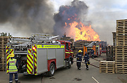 fire crews from Northmaptonshire and Leicestershire fight a large pallet fire on the site of a former RAF airfield near desboorugh in Northamptonshire