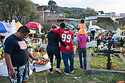 A churros vendor sells snacks in the cemetery as family members enjoy a picnic at the gravesite of relatives during Day of the Dead festival November 2, 2017 in Quiroga, Michoacan, Mexico.  The festival has been celebrated since the Aztec empire celebrates ancestors and deceased loved ones.