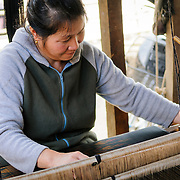 A woman uses her loom in hand-weaving silk fabric in northeastern Laos.