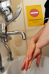 Nurse washing her hands in community hospital Bradford UK