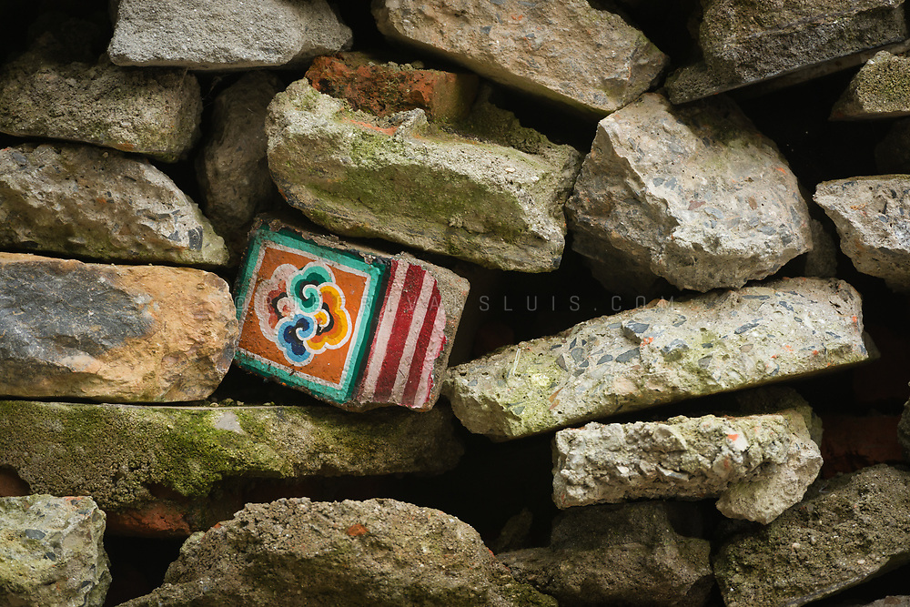 A decorated piece of wall amongst a pile of post-earthquake rubble in Shechen Monastery, Kathmandu, Nepal. Photo © robertvansluis.com