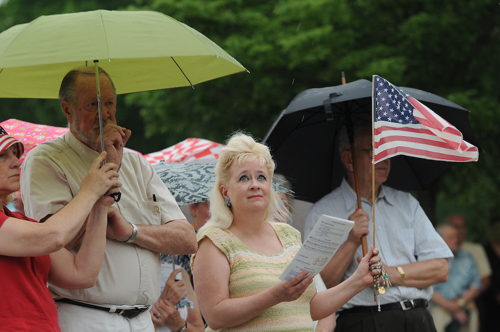 An attendees of a Memorial Day Field Mass at St. Adalbert Cemetery keeps a watchful but patriotic eye on threatening skies in Niles.