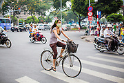 27 MARCH 2012 - HO CHI MINH CITY, VIETNAM:  A woman on a bicycle in Ho Chi Minh City, Vietnam. As Vietnam's economy has started to boom people have moved from bicycles to motor scooters for personal transport. Ho Chi Minh City, which used to be known as Saigon, is the largest city in Vietnam and the commercial hub of southern Vietnam.      PHOTO BY JACK KURTZ