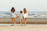 Two sisters hold their brothers hands as they walk across the sand down to the water's edge.