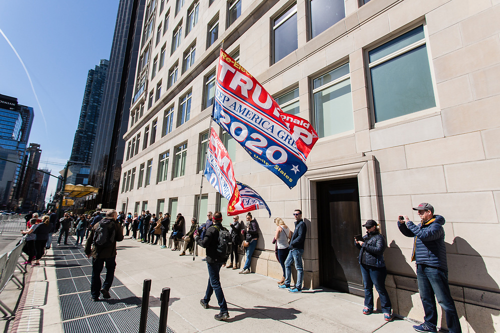 New York, NY - 24 March 2019. Senator Kirsten Gillibrand (D-NY) held a presidential campaign rally on New York's Central Park West in Front of the Trump Hotel  and Tower. A Trump supporter walks down the dignwalk outside the rally with large pro-Trump flags.