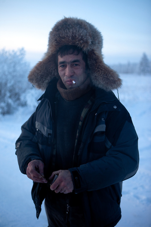 The Pole of Cold. Portrait of a local fisherman smoking a cigarette close to the  village of Tomtor. The area is extremely cold during the winter. Two towns by the highway, Tomtor and Oymyakon, both claim the coldest inhabited place on earth (often referred to as -71.2°C, but might be -67.7°C) outside of Antarctica. The average temperature in Oymyakon in January is -42°C (daily maximum) and -50°C (daily minimum). The images had been made during an outside temperature in between -50°C up to -55°C. Tomtor, Jakutien, Yakutia, Russian Federation, Russia, RUS, 20.01.2010