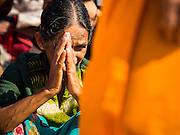 "02 JANUARY 2015 - KHLONG LUANG, PATHUM THANI, THAILAND: An Indian  woman prays as monks walk past her at Wat Phra Dhammakaya on the first day of the 4th annual Dhammachai Dhutanaga (a dhutanga is a ""wandering"" and translated as pilgrimage). More than 1,100 monks are participating in a 450 kilometer (280 miles) long pilgrimage, which is going through six provinces in central Thailand. The purpose of the pilgrimage is to pay homage to the Buddha, preserve Buddhist culture, welcome the new year, and ""develop virtuous Buddhist youth leaders."" Wat Phra Dhammakaya is the largest Buddhist temple in Thailand and the center of the Dhammakaya movement, a Buddhist sect founded in the 1970s.   PHOTO BY JACK KURTZ"