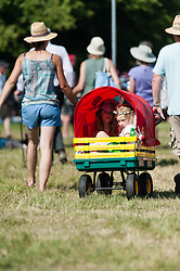 © Licensed to London News Pictures. 18/07/2014. Southwold, UK.   Two young children shelter from the hot sun in a cart pulled around by their parents at Latitude Festival 2014 Day 1.   Today is predicted to be the hottest day of the year with temperatures expected to reach 32 degrees centigrade.  Latitude is an British annual music festival.  Photo credit : Richard Isaac/LNP