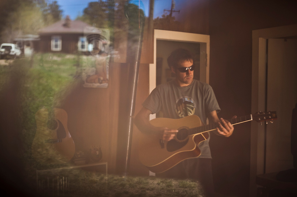 Kevin Gillette plays guitar in his home in Gold Hill, Colorado.