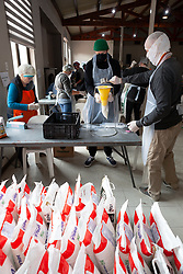 Volunteers portion out dry food into sachets as they prepare food parcels at a church, to be distributed to Vanwyk'svlei in Wellington, Western Cape, South Africa.(Picture: JULIAN GOLDSWAIN)