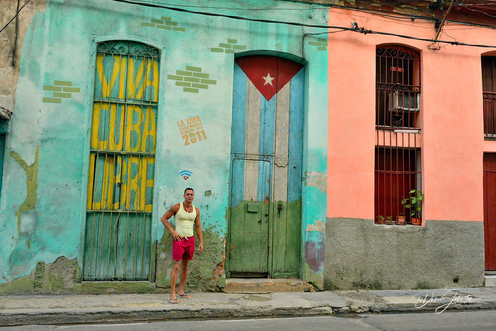 Street photography in central Havana- Colonial architectural details- painted walls and doorway with pedestrian, La Habana (Havana), Habana, Cuba