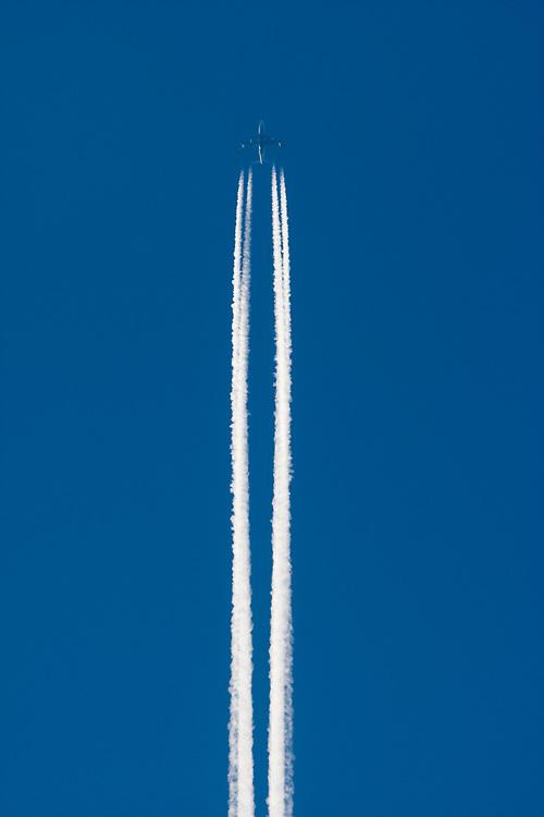 USA, Alaska, Contrail from passenger jet flying overhead at sunset