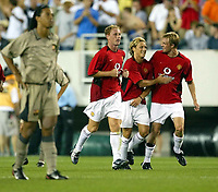 Photo Aidan Ellis.<br />Manchester United v Barcelona (at the Lincoln Financial Field Philadelphia) 03/08/03.<br />United's Diego Forlan is congratualted by team mates Darren Fletcher and Nicky Butt after scoring his and United's second goal Ronaldinho is the fore ground with his hands on his hips