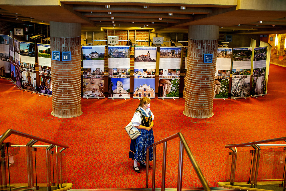 """A woman in traditional clothes infront of an exhibition at the 71st Sudeten German meeting at the """"Philharmonie im Gasteig"""" in Munich."""