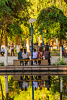Uyghur people relaxing in Renmin Park. Turpan, Xinjiang Province, China. Turpan is a small oasis town and former Silk Road outpost. Uyghur people are a Central Asian people of Muslim Turkic origin. They are China's largest minority group.