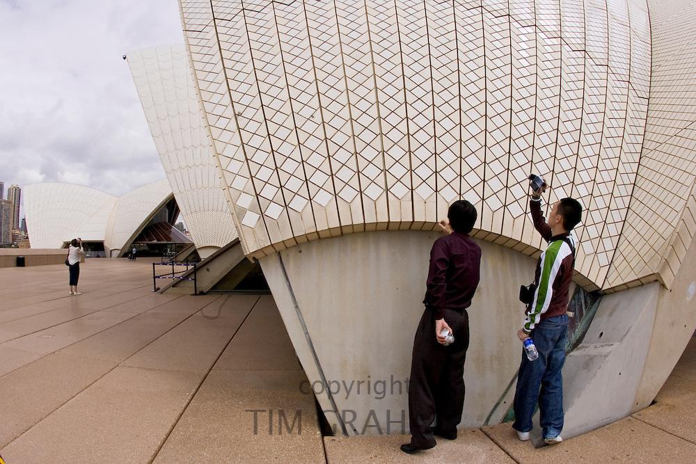 Tourists take photographs outside Sydney Opera House, Australia