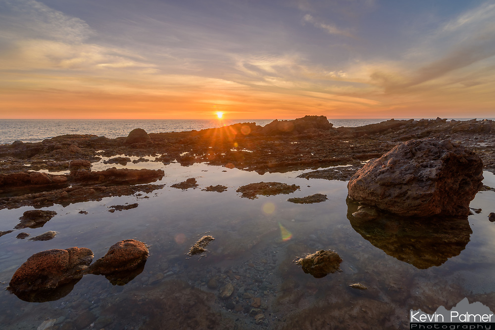 The sun sets over a tide pool in Laguna Beach, California. Underneath the water are hermit crabs, sea anemones, and other sea creatures stranded until the waves rise again. I came here at low tide during a full moon, so the tide doesn't get much lower than this. Normally this part of Victoria Beach would be difficult to access as much of it would be underwater. Both low and high tide occur twice a day approximately 6 hours apart. During a full moon or a new moon the tides are especially high and low. The gravitational force of the sun and the moon combine to generate more of a pull on earth's oceans. This is called a spring tide. But during a quarter moon, the moon is at a right angle with the earth and the sun and there is less variation between high and low tides. This is called a neap tide.