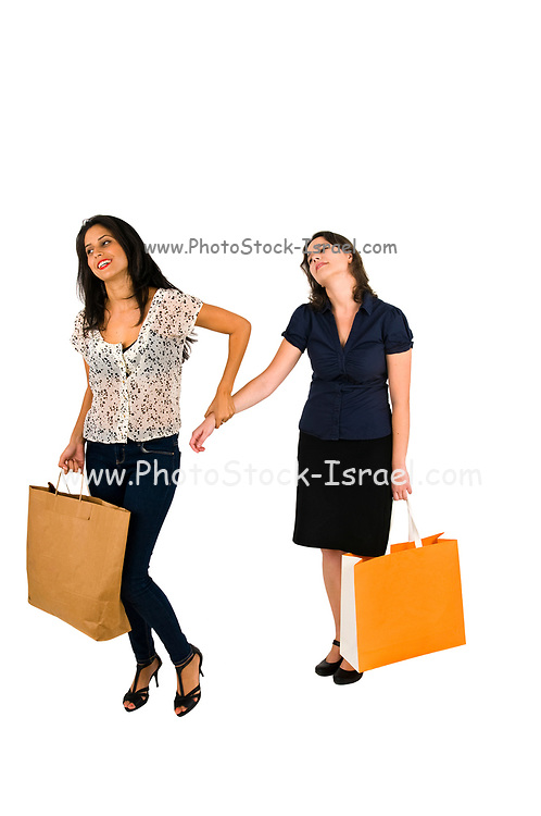 Two multiracial female friends shopping together. The one friend pulls the hand of the other tired friend