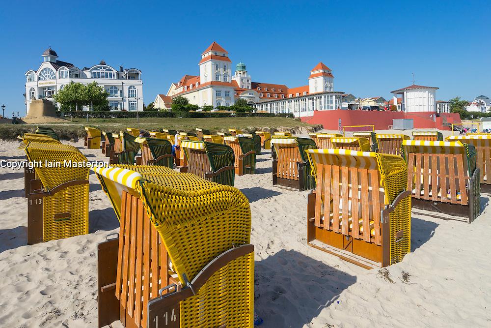 View of traditional Strandkorb chairs on beach and Kurhaus Binz Hotel at Binz seaside resort on Rugen Island in Germany