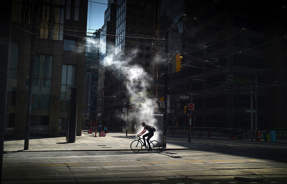 A cyclist passes a steam vent on the empty streets of the financial district during the annual Victoria Day holiday in Toronto, Ont. (2013)
