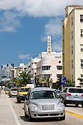 Chrysler PT Cruiser Classic auto passes Art Deco architecture in Collins Avenue, South Beach, Miami, Florida, USA