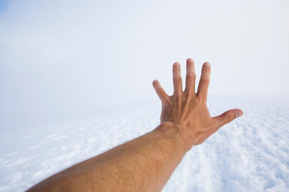 An arm and hand reaching forward into the fog on a snowy, well trodden trail in Mt. Rainier National Park.