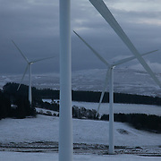 Wind turbines harnessing the wind in the Scottish Borders, 28th of December 2020, Scotland, United Kingdom. The wind farm, Longpark Wind Farm, is long established and part of the renewable energy production in Scotland. The farm sits in the hills above the village Stow, near Galashields in the Scottish Borders. In between the wind turbines sheep grass in the fields lightly covered by snow.