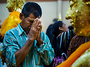 31 MAY 2017 - CHACHOENGSAO, THAILAND: A man prays at Wat Sothon (also spelled Sothorn) in Chachoengsao, Thailand. The temple is one of the largest and most visited in Thailand. People make merit by paying to wrap the Buddha statues in orange robes. The temple is most famous because people leave hard boiled eggs as an offering at the temple. They ask for business success or children and leave hundreds of hard boiled eggs.      PHOTO BY JACK KURTZ