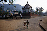 Two young boys walk downhill, passing the Rameshwar Mahdev temple in Kathmandu, Nepal. Holding hands, the friends make their way back towards the city from this quieter suburb. The road is swept and there is no litter or mess surrounding the temple located in the Himalayan foothills.