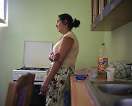 The maid of the Grafian Mihai family, standing in the kitchen of the house she works in, in the village of Sintesti, in Romania, early August 2006.  The Kalderari roma of Sintesti are by tradition metal workers, originally making alcohol stills, pots and pans, but now dealing in scrap metal. The large profits from their business have enabled them to take on maids and family helpers, as well as to build large houses in the village of Sintesti, 20km from Bucharest, and to invest in fast, Western brand name cars such as BMW's, Mercedes and Porsche.