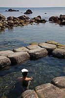 At the Todohokke Onsen, the bath right at the seashore where soakers can enjoy open air bathing with the added attraction of views of  the sea and Mt. Esan in the background. The temperature of the bath varies with the tide as ocean water enters, it cools the bath waters down.