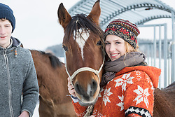 Young couple standing with horse and smiling, Bavaria, Germany